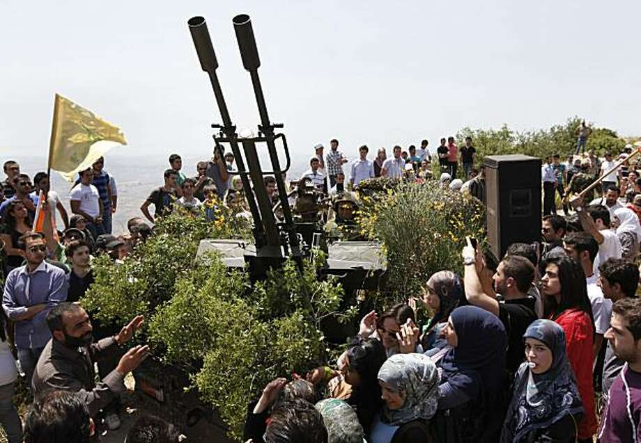 "Lebanese university students, gather around an anti-aircraft gun as a Hezbollah fighter explain to them the group's various tactics and weapons used against Israeli soldiers on the battlefield, during a trip to Hezbollah strongholds, in Sojod village, southern Lebanon, on Saturday, May 22, 2010. With a sprawling war museum of its history and student tours to its strongholds, Hezbollah is promoting itself through ""jihadi tourism"" to mark the 10th anniversary of Israel's withdrawal from southern Lebanon. It's a way to showcase its military prowess at a time when Israel and the U.S. say Iranian-backed group is acquiring more sophisticated weaponry. Photo: Hussein Malla, AP"