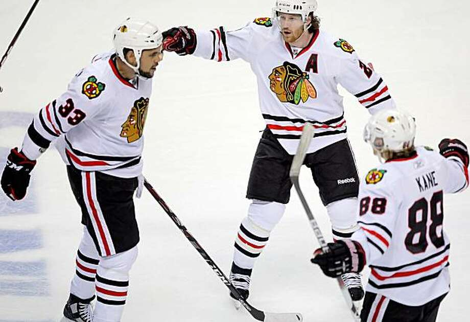 Dustin Byfuglien, left, celebrates his game-winning goal with teammates, Troy Brouwer, center, and Patrick Kane in the third period of Game 1 of the Western Conference finals in San Jose on Sunday. Photo: Carlos Avila Gonzalez, The Chronicle