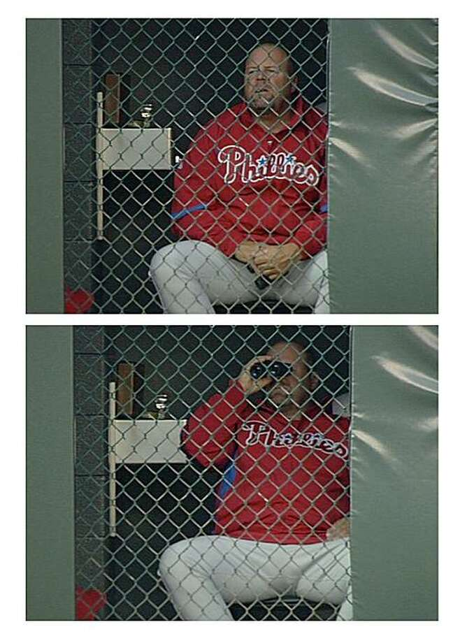 This two-picture sequence  provided by FSN Rocky Mountain Sports shows Philadelphia Phillies bullpen coach Mick Billmeyer using binoculars in the bullpen during Monday night's, May 10, 2010, baseball game between the Philadelphia Phillies and the ColoradoRockies. Photo: FSN Rocky Mountain, AP