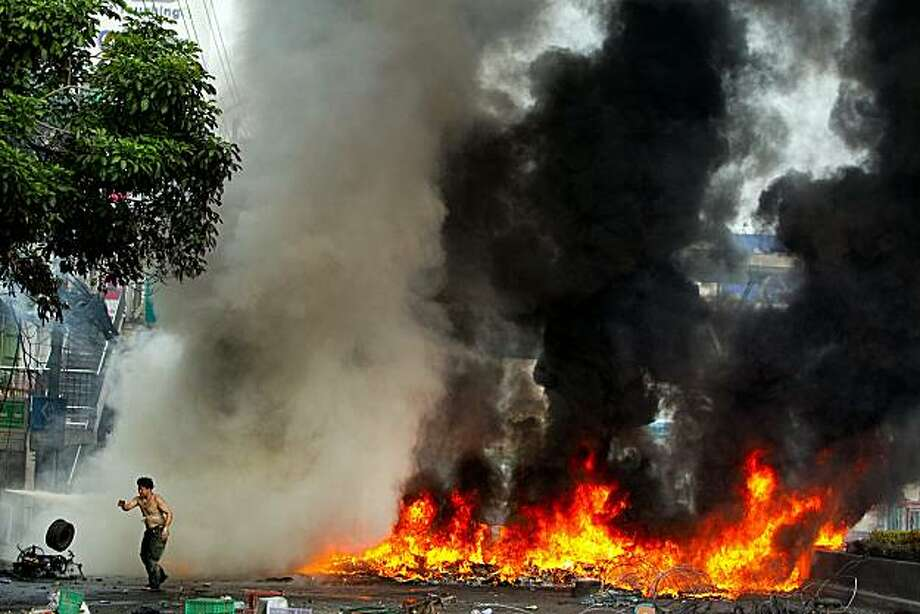 "BANGKOK, THAILAND - MAY16: A major street in Bangkok is seen with tires burning as the violence in central Bangkok continues on May 16, 2010 in Bangkok, Thailand. So far at least 154 have been injured and over 20 killed in the clashes as the military andthe government launched an operation to disperse anti-government protesters who have closed parts of the city for two months. A state of emergency is in effect that spreads to 17 provinces in the country. The Thai army declared certain protest areas whereclashes are taking place as a ""Live Fire Zone."" Photo: Paula Bronstein, Getty Images"