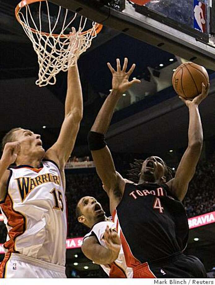Toronto Raptors Chris Bosh goes to the net against Golden State Warriors Brandon Wright (C) and Andris Biedrins (L) during the first half of their NBA basketball game in Toronto October 31, 2008.     REUTERS/Mark Blinch (CANADA) Photo: Mark Blinch, Reuters