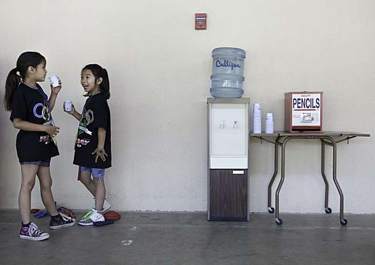 Porterville, CA--- Tela Hunter, 7, lf, and her cousin Shealuhn Hunter, 7, share a word at the water cooler during a field day at Citrus South Tule School. Students competed in different activities that emphasized exercise and the spirit of competition with an Olympic theme. Students drink bottled water at the school because the groundwater basin under the school is loaded with nitrates. Two sources of groundwater pollution are the use of nitrogen-based fertilizer by farmers and by cattle manure.