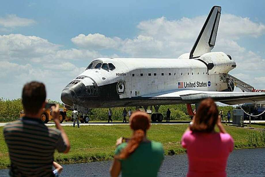 CAPE CANAVERAL, FL - MAY 26:  People take pictures as Space Shuttle Atlantis is towed back to the Orbiter Processing Facility (OPF) after it returned to the shuttle landing facility at Kennedy Space Center May 26, 2010 in Cape Canaveral, Florida. The astronauts have just completed a twelve day mission to the International Space Station, this was the final scheduled mission for Atlantis. Photo: Joe Raedle, Getty Images