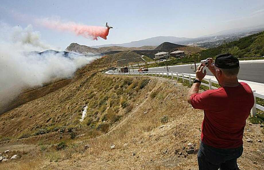 Resident Warren Gillette photographs as a plane drops fire retardant onto a brush fire on a hillside near homes on Skyridge Drive in the Home Gardens community of Riverside County near Corona, Calif., May 20, 2010. (AP Photo/The Press-Enterprise, Silvia Flores)  MANDATORY CREDIT; NO SALES; MAGS OUT Photo: Silvia Flores, AP
