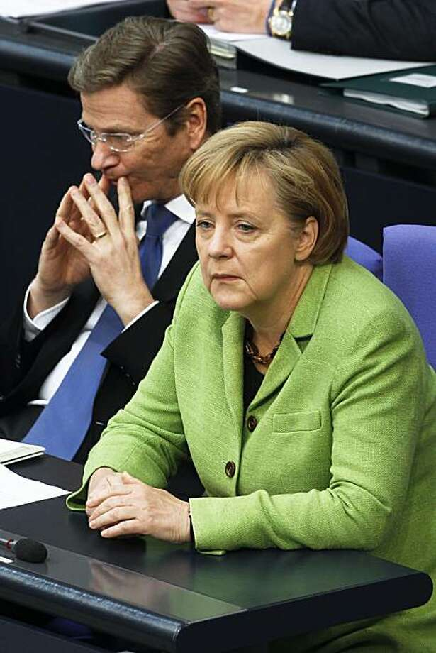 German Chancellor Angela Merkel, right, and Vice Chancellor and Foreign Minister Guido Westerwelle react during the final parliament debate of an euro 750 billion (US $1 trillion) eurozone rescue package  in Berlin, Friday, May 21, 2010. Photo: Markus Schreiber, AP