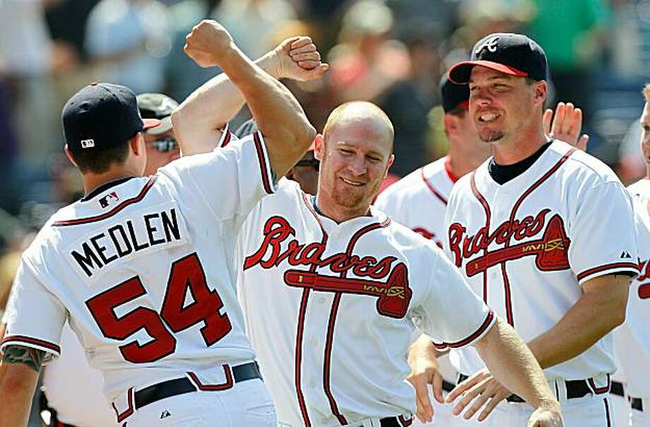 ATLANTA - MAY 20:  Pinch hitter Brooks Conrad #26 of the Atlanta Braves celebrates with Kris Medlen #54 and Chipper Jones #10 after hitting a walk-off grand slam to give the Braves a 10-9 win over over the Cincinnati Reds at Turner Field on May 20, 2010 in Atlanta, Georgia. Photo: Kevin C. Cox, Getty Images