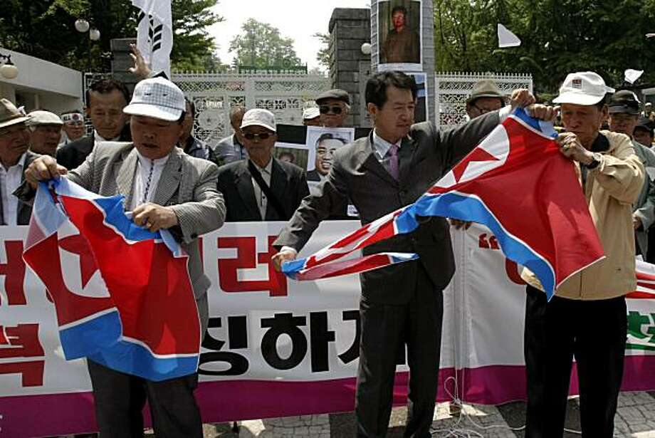 South Korean conservative activists tear North Korean flags during a rally against the communist neighbor in front of the Defense Ministry in Seoul, South Korea, Thursday, May  20, 2010. South Korea accused North Korea on Thursday of firing a torpedo thatsank a naval warship in March, killing 46 sailors in the country's worst military disaster since the Korean War. Photo: Ahn Young-joon, AP
