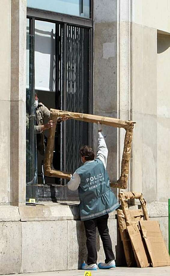 A police officer hands the packed frames of the stolen paintings, to a colleague, from outside the Paris Museum of Modern Art,  following the stealing of five paintings Thursday May 20, 2010. Police and prosecutors say a lone thief has stolen five paintings worth a total of Euros 500 million ($613 million), including works by Picasso and Matisse. Other frames  of the paintings arevisible at right. Photo: Jacques Brinon, AP