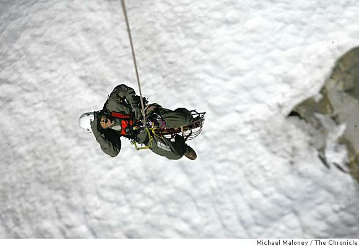 John Dill of the Yosemite National Park's Search and Rescue Team is transported across a snow field with a stetcher attached below him in Yosemite National Park, Calif., on May 24, 2007.