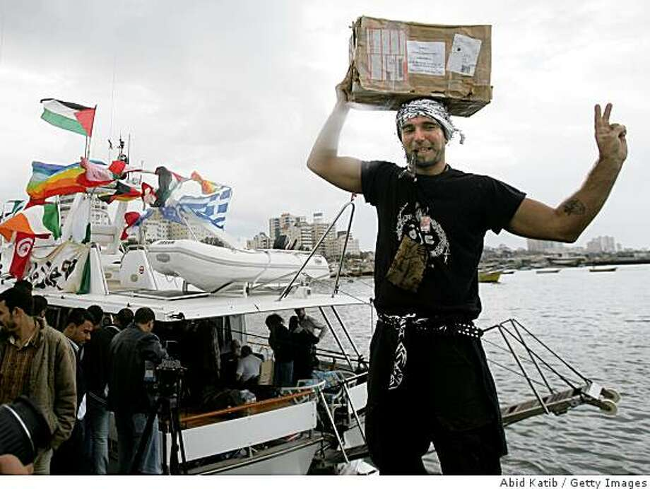 GAZA CITY, GAZA STRIP - OCTOBER 29:   An International peace activist carries medical supplies after they arrived by boat in the seaport on October 29, 2008 in Gaza City, Gaza Strip.  Some 27 international activists sailed from Larnaca in Cyprus on Tuesday with medical supplies in an attempt to break the Israeli blockade over Gaza, arriving Wednesday. They are scheduled to remain in Gaza for four days in an attempt to bring attention to Israel's blockade of the Hamas-controlled territory. Although Israel said it would block the boat, navy ships did not interfere.  (Photo by Abid Katib/Getty Images) Photo: Abid Katib, Getty Images
