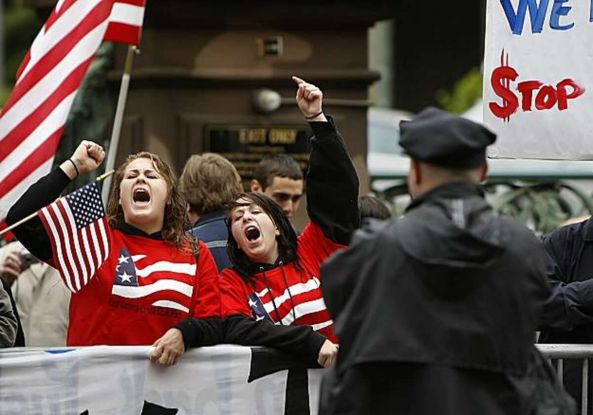Danielle Donaldson, left, and Kaitlyn MacKusick yell in protest of President Obama outside the Fairmont Hotel on Tuesday.