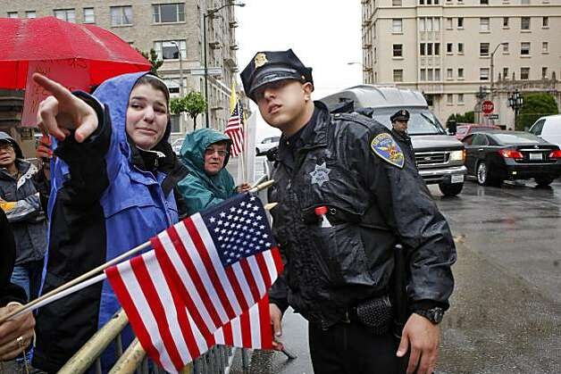 Cristina Minasian asks help from officer Adam Eatia at the protest across the street from the Fairmont Hotel, where President Obama made an appearance Tuesday. Photo: Lacy Atkins, The Chronicle