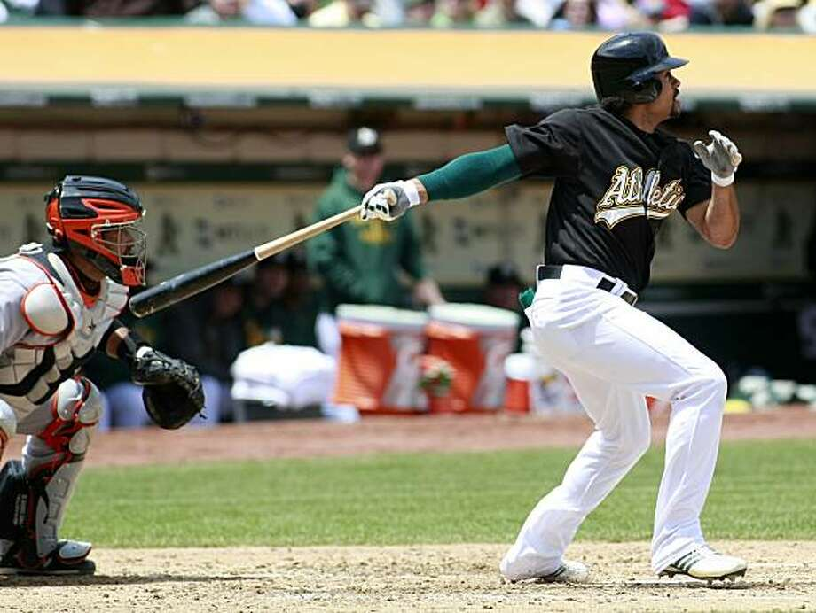 Oakland Athletics' Coco Crisp, right, hits sacrifice fly that knocked in a run as San Francisco Giants catcher Bengie Molina watches behind the plate during the third inning of a baseball game in Oakland, Calif., Saturday, May 22, 2010. The Athletics won1-0. Photo: Darryl Bush, AP