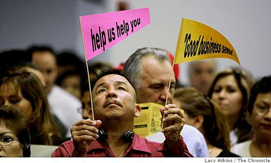 Juan Carlos reads the signs that were give to him along the the hundreds of people that gather for help and information concerning foreclosures, at the Holy Rosary Parish, Monday Oct. 27, 2008, in Antioch, Calif. He is looking at the possibility next month of foreclosure of his home in Antioch Photo: Lacy Atkins, The Chronicle