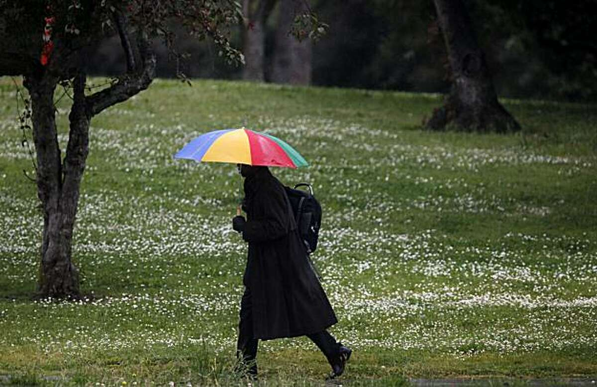 James Mason uses his umbrella to a combat a late spring shower during the lunch hour on Grand Avenue on Monday May 17, 2010 in Oakland, Calif.