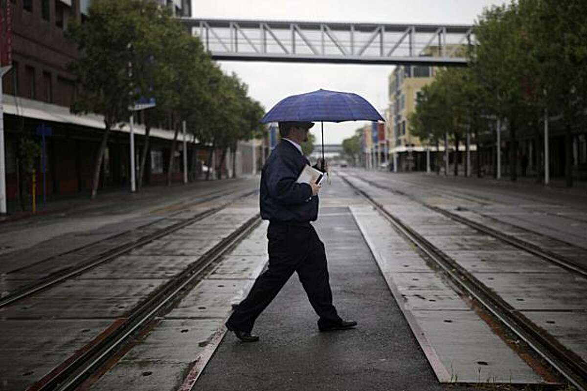 David Callahan of Berkeley takes cover from the rain under an umbrella as he crosses Embarcadero West before the start of his shift in Oakland on Monday.