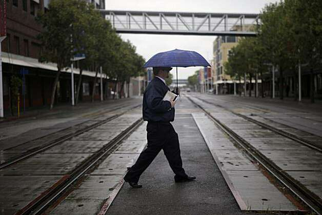 David Callahan of Berkeley takes cover from the rain under an umbrella as he crosses Embarcadero West before the start of his shift in Oakland on Monday. Photo: Lea Suzuki, The Chronicle
