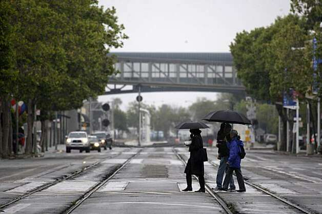 Pedestrians take cover from the rain underneath umbrellas as they walk across Embarcadero West in Oakland on Monday. Photo: Lea Suzuki, The Chronicle
