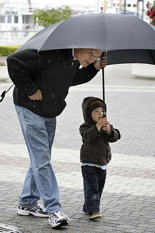 Luke Tanaguchi-Bauer (right), 2, of Oakland holds an umbrella to cover himself and his grandfather, Steven Phillips (left) of Sacramento, from the rain in Oakland on Monday. Photo: Lea Suzuki, The Chronicle