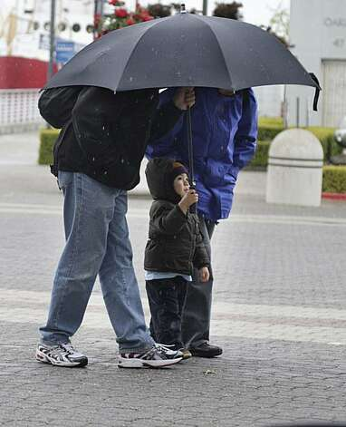 Luke Tanaguchi-Bauer (center), 2, of Oakland covers himself and his grandparents, Steven Phillips (left) and Dorothy Phillips (right), both of Sacramento, from the rain in Oakland on Monday. Photo: Lea Suzuki, The Chronicle