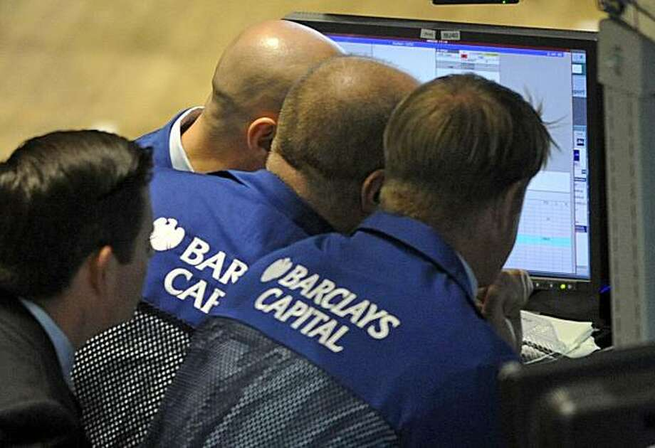 FILE - In this May 6, 2010 file photo, traders from Barclays Capital work on the floor of the New York Stock Exchange, in New York. Using super-fast computers, high-frequency traders in effect bend down to pick up pennies lying about in the stock market,then do it again, sometimes thousands of times a second. Photo: Henny Ray Abrams, AP