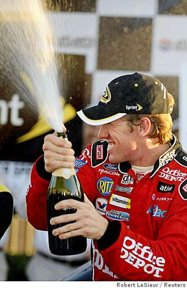 Carl Edwards lets the victory champagne fly after winning the NASCAR Sprint Cup Pep Boys Auto 500 at Atlanta Motor Speedway in Hampton Georgia, October 26, 2008. Photo: Robert LeSieur, Reuters