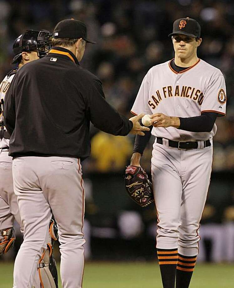 San Francisco Giants' Barry Zito, right, hands the baseball to manager Bruce Bochy after being taken out for a relief pitcher against the Oakland Athletics in the seventh inning a baseball game in Oakland, Calif., Friday, May 21, 2010. Photo: Jeff Chiu, AP