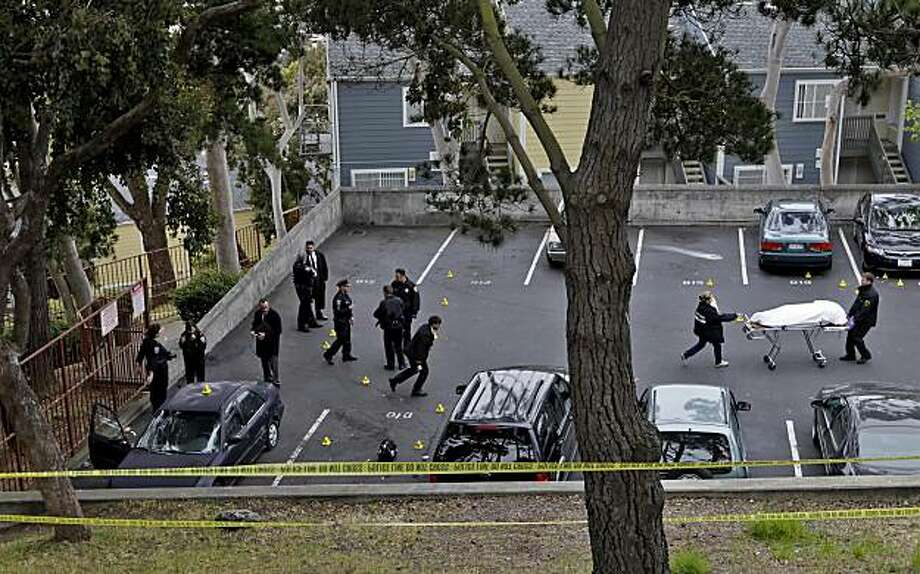Police officers and Medical Examiner remove the body from the car where a young man was gunned down in the parking lot at the corner of Ingalls and La Salle in what is called the Oakdale District of Hunters Point, Saturday morning, May 15, 2010, in San Francisco, Calif. Residents heard the 40 rounds of gunfire around 3:30 a.m., but didn't call the police, because of fear. Photo: Lacy Atkins, The Chronicle