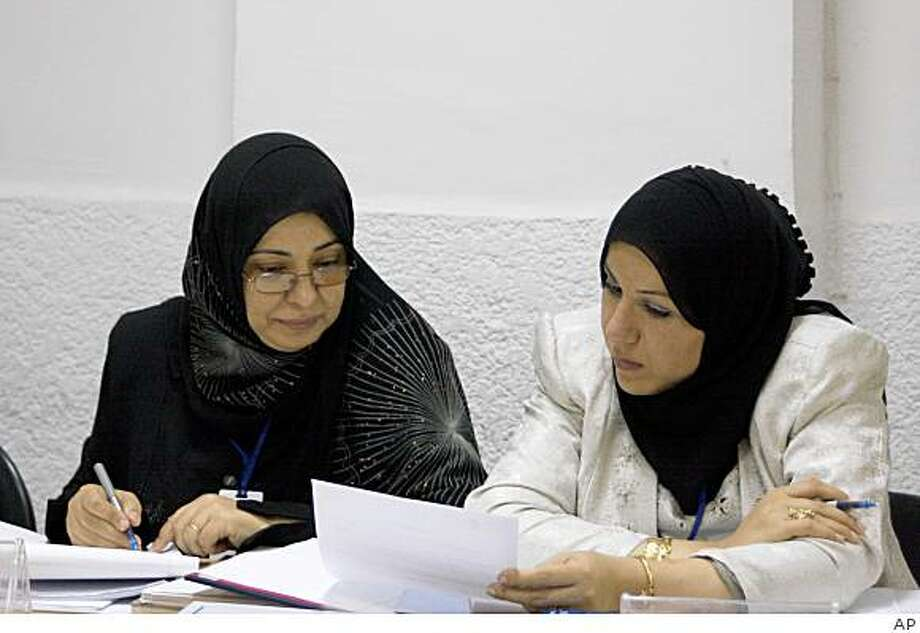 In this photo provided by United States Agency for International Development, Shetha Nasser, right, a 46-year-old engineer at the Water Resources Ministry, discusses a problem with a fellow student during a class in Baghdad, Iraq, about decision-making on Tuesday, Sept. 16, 2008. The class is run by the U.S. Agency for International Development's Tatweer project as part of efforts to train Iraqi civil servants to improve Iraq's ability to spend its oil riches amid criticism U.S. taxpayers are shouldering an unfair burden. (AP Photo/US AID) Photo: AP