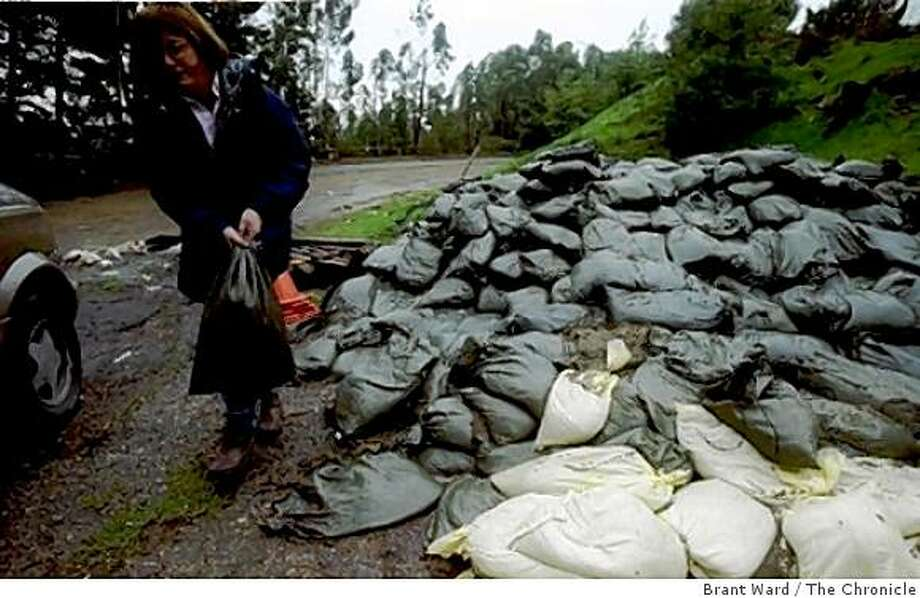In this file photo from 1998, Holly Ourisman of Oakland wrestled her 20 sandbags into her car. She lives near a creek which nearly overflowed, so she went to the Oakland maintenance yard at Joaquin Miller Park where sandbags are available. Photo: Brant Ward, The Chronicle