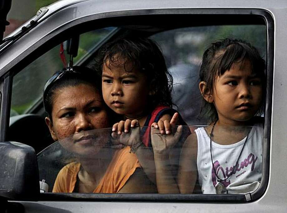 """A family watches anti-government protesters from their ca in Bangkok, Thailand, Monday, May 17, 2010. The Thai government on Monday warned protesters barricaded within their """"occupation zone"""" in the heart of the capital to leave by 3 p.m., saying anyone who remains there will be violating the law and will face two years in prison. Photo: Manish Swarup, AP"""