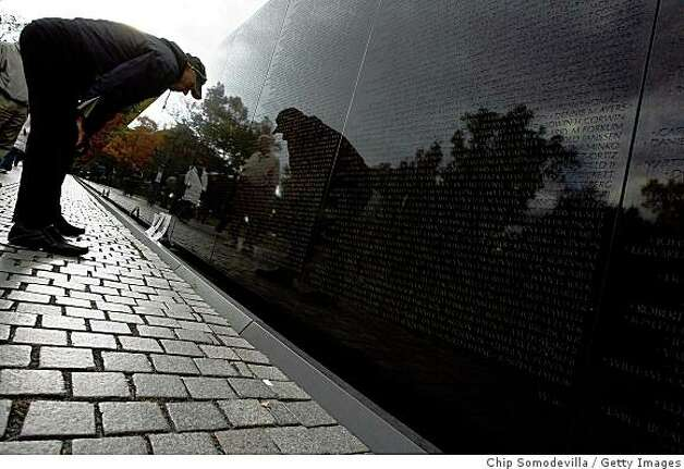 "WASHINGTON - NOVEMBER 7:  Visitors look closely at the names inscribed on the Vietnam Veterans Memorial during ceremonies to mark The Wall's 25th anniversary on the National Mall November 7, 2007 in Washington, DC. Organizers commemorated the 25th anniversary with ""The Reading of the Names,"" the four-day event during which the over 58,000 names inscribed on the Vietnam Veterans Memorial are read aloud. For the fourth time in The Wall's history all of the names were read in Washington, D.C. Photo: Chip Somodevilla, Getty Images"