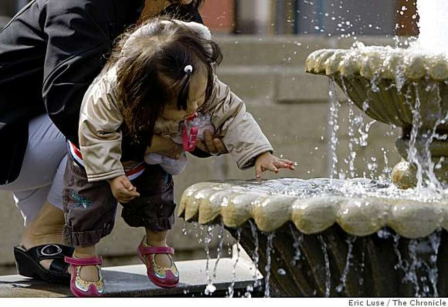 Family friend Helen Lee holds Kaylee Kim,15months, to touch the water from the center fountain at Marina Square Center in San Leandro photographed on Friday, October 17, 2008. Photo: Eric Luse, The Chronicle