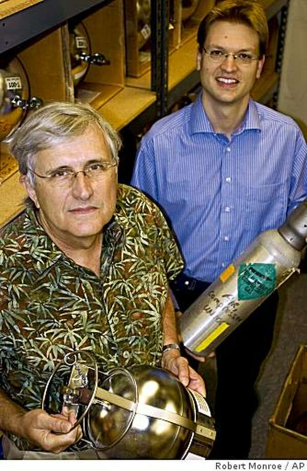 This undated handout photo provided by the Scripps Institute shows Scripps geoscientists Ray Weiss, left, and Jens Muehle  in San Diego, Calif., amid collection cylinders used to collect air samples from a variety of locations around the world. Weiss and Muehle led a study that found that the greenhouse gas nitrogen trifluoride, used in the manufacture of flat-panel monitors, escapes to the atmosphere at levels much higher than previously assumed. Two major and potent greenhouse gases are building in the atmosphere, raising an unexpected new threat for accelerating global warming, new studies show. The gases are methane and nitrogen trifluoride, and their levels are building faster than expected. (AP Photo/Scripps Institute, Robert Monroe) Photo: Robert Monroe, AP