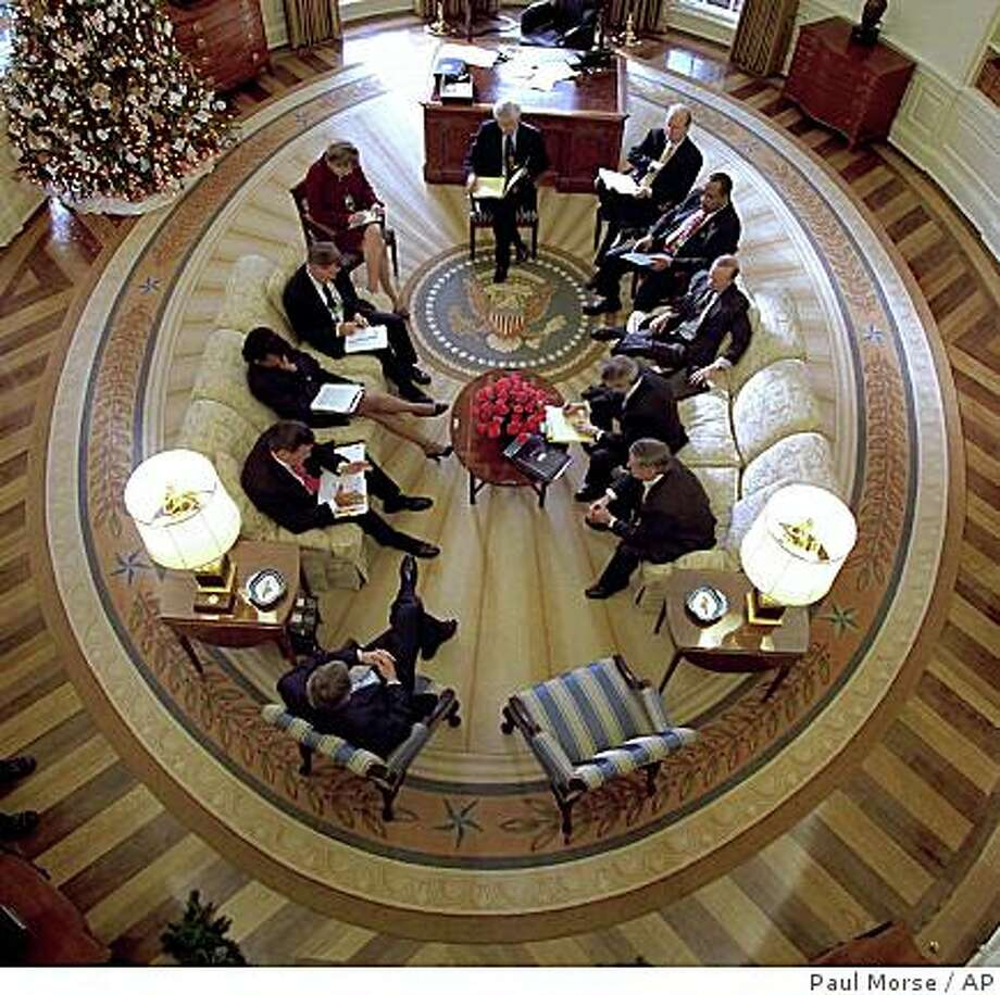 President Bush hosts a meeting in the Oval Office decorated with the new presidential rug in the White House in Washington, Thursday, Dec. 20, 2001. The rug, which is unique to the Bush administration, arrived earlier in the week and was unveiled to the media Friday Dec. 21, 2001. Photo: Paul Morse, AP