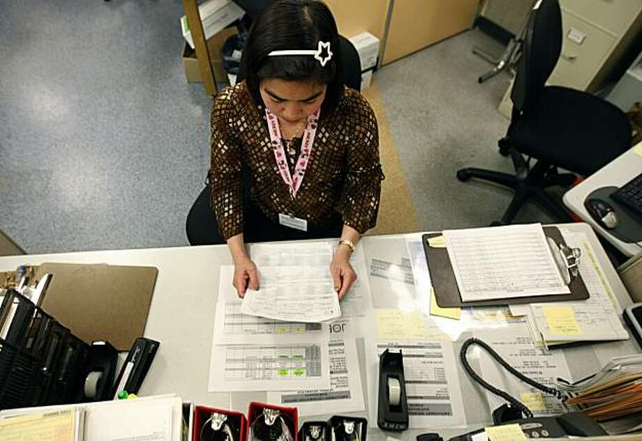 Emelyn Ejada works in the San Francisco Human Services Agency office Friday. Ejada was hired as a six-month temporary employee through the CalWORKS program but could lose her job if Gov. Schwarzenegger's proposed budget cuts are enacted. Photo: Paul Chinn, The Chronicle