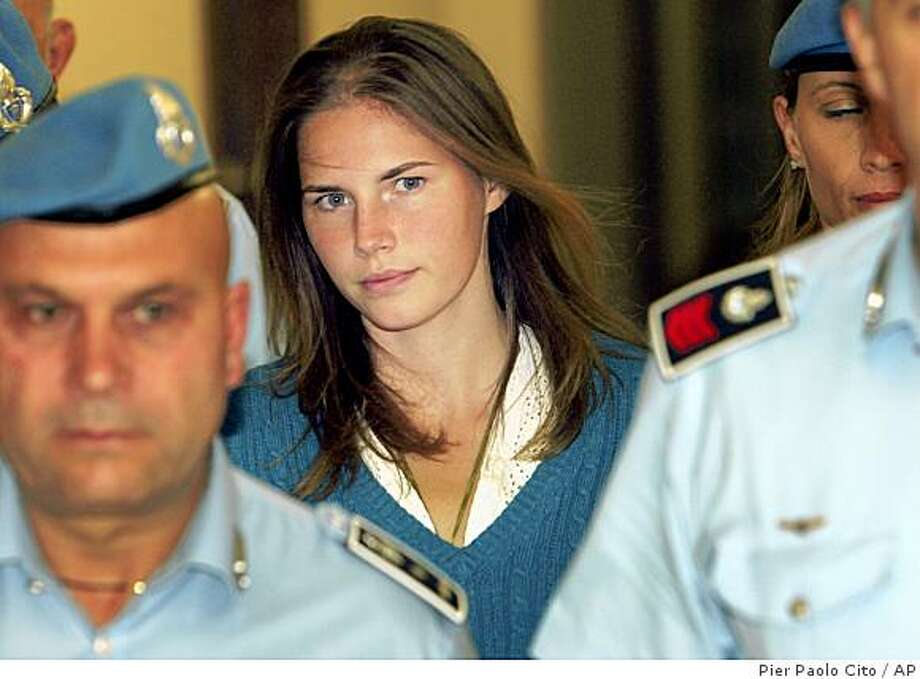 In this Sept. 26, 2008 file photo, American murder suspect Amanda Knox is escorted by Italian penitentiary police officers to Perugia's court at the end of a hearing, central Italy. Italian news reports on Saturday, Oct. 18, 2008 say Knox, who is suspected in last year's slaying of her British flatmate Meredith Kercher, has again proclaimed her innocence. The news agencies, reporting from Perugia on a closed-door court hearing Saturday, said Amanda Knox greeted the judge in Italian, then spoke in English to deny any role in the slaying. Knox, her former Italian boyfriend, and a young man from the Ivory Coast are all suspects in the murder of the British student.   (AP Photo/Pier Paolo Cito, files) Photo: Pier Paolo Cito, AP