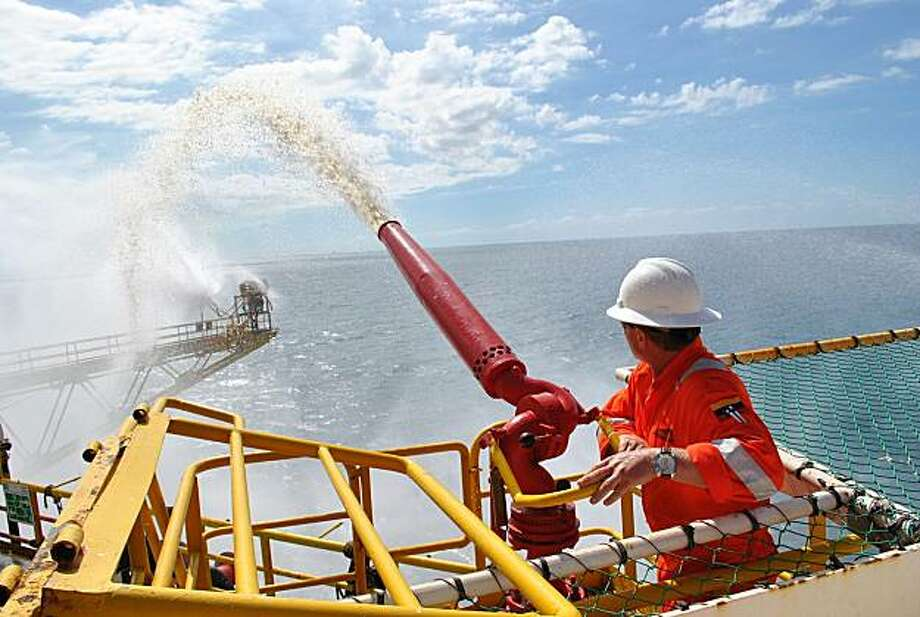 In this undated photo released by Petroleos de Venezuela, S.A. PDVSA, an oil worker points a water cannon at the Aban Pearl platform, off eastern Sucre state, Venezuela. The Aban pearl platform sank off Venezuela on Thursday, and 95 workers were rescued safely and the sinking poses no threat to the environment, according to Venezuela's Oil Minister Rafael Ramirez. Photo: AP