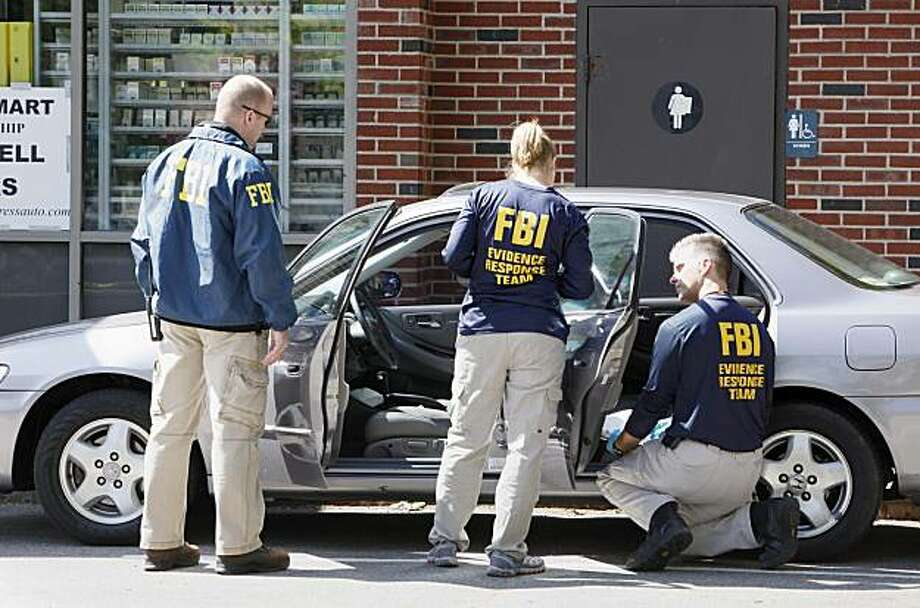 FBI investigators search a car at a service station in Brookline, Mass., Thursday, May 13, 2010, in connection with the failed New York Times Square car bomb. Photo: Michael Dwyer, AP