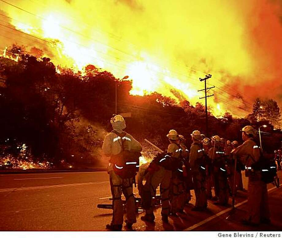 Firefighters watch as a hillside burns during a brush fire in the Sepulveda Pass on the western edge of Los Angeles in the early morning of October 23, 2008. One hundred acres burned, threatening homes, but the blaze was extinguished without loss or injury.   REUTERS/Gene Blevins    (UNITED STATES) Photo: Gene Blevins, Reuters