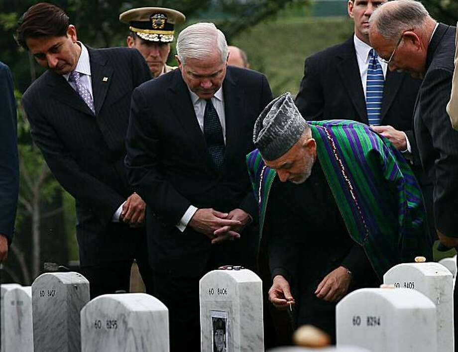 ARLINGTON, VA - MAY 13: During a tour of Section 60 at Arlington National Cemetery with U.S. Secretary of Defense Robert Gates (2nd-L), Afghanistan President Hamid Karzai (3rd-L) visit the grave of PFC Justin Davis who died in 2006 while fighting in Afghanistan May 13, 2010 in Arlington, Virginia. Section 60 is where the majority of U.S. troops killed in Afghanistan and Iraq are buried, including 140 casualties from Afghanistan. Photo: Win McNamee, Getty Images