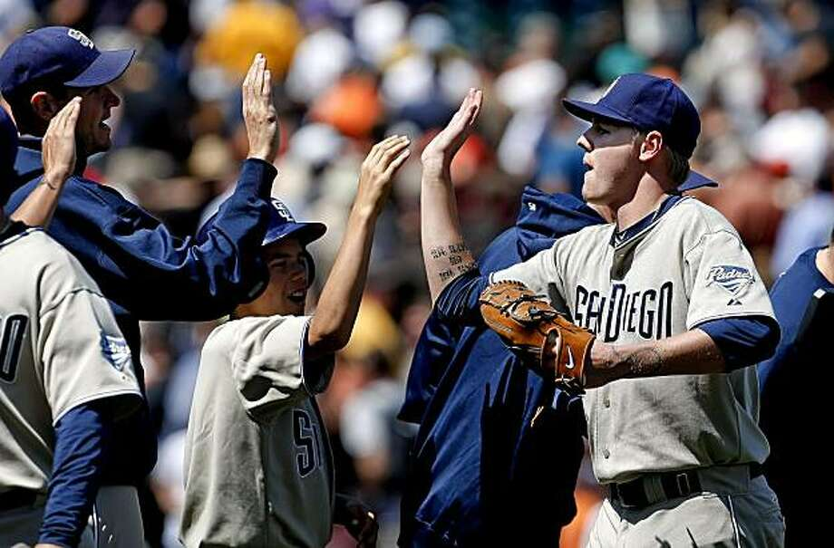 The San Diego Padres' Mat Latos (right) high fives his teammates after his win Thursday in San Francisco. Photo: Michael Macor, The Chronicle