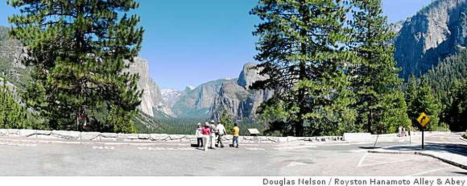 Tourists look out at Half Dome in Yosemite National Park in August 2006 before the Tunnel View Overlook was redesigned. A half dozen trees were removed and a dedicated viewing area was built to give tourists easier access to the picturesque viewing spot. Photo: Douglas Nelson, Royston Hanamoto Alley & Abey
