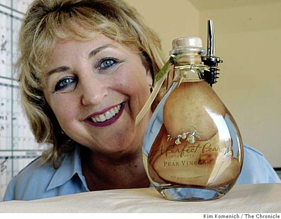 """Susan Knapp of Napa, Calif., stands behind one of her specialty products-- pear vinegar. Knapp started a business selling cinnamon pear jelly from her kitchen that has evolved into """"A Perfect Pear,"""" a business with annual sales reaching $700,000 today. Orders are backing up because Knapp can't get the capital to buy merchandise. As credit markets have seized up, she has invested her own money and is calling friends, relatives and private investors for help. Photographed at A Perfect Pair in Napa Calif., on Wednesday, Oct. 22, 2008. Photo: Kim Komenich, The Chronicle"""