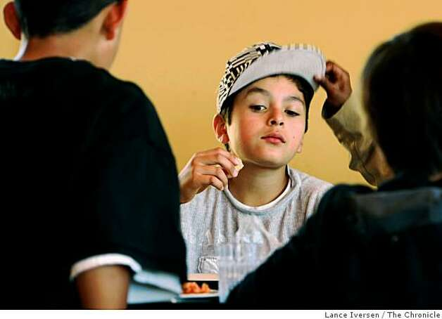 Carlos Montano, 11, dines on a slice of pizza made from scratch as a friend lifts his hat. Photo: Lance Iversen, The Chronicle