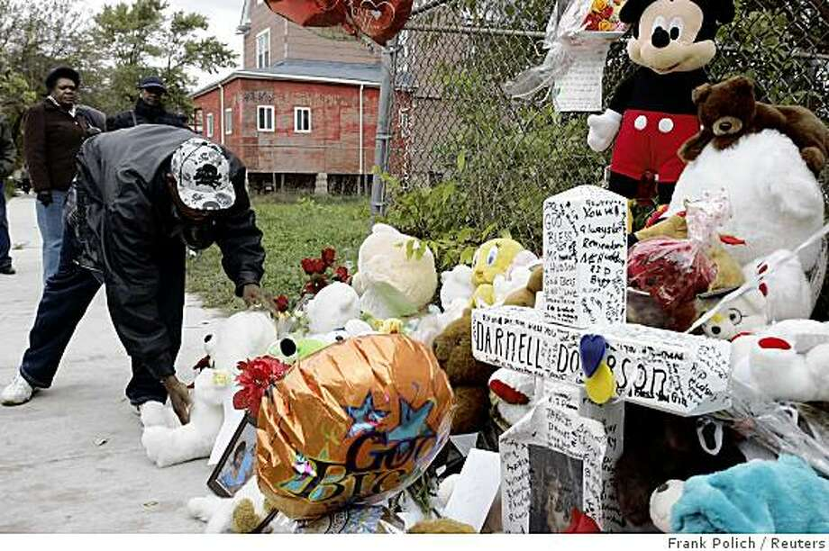 A man places a teddy bear at a memorial outside the home of actress and singer Jennifer Hudson in the Englewood neighborhood of Chicago, Illinois October 27, 2008. Hudson's mother and brother were found slain in their home October 24. Police on Monday found the body of a young boy following a search for Academy Award-winner Hudson's 7-year-old nephew, who has been missing since Hudson's mother and brother were slain last week. REUTERS/Frank Polich (UNITED STATES) Photo: Frank Polich, Reuters