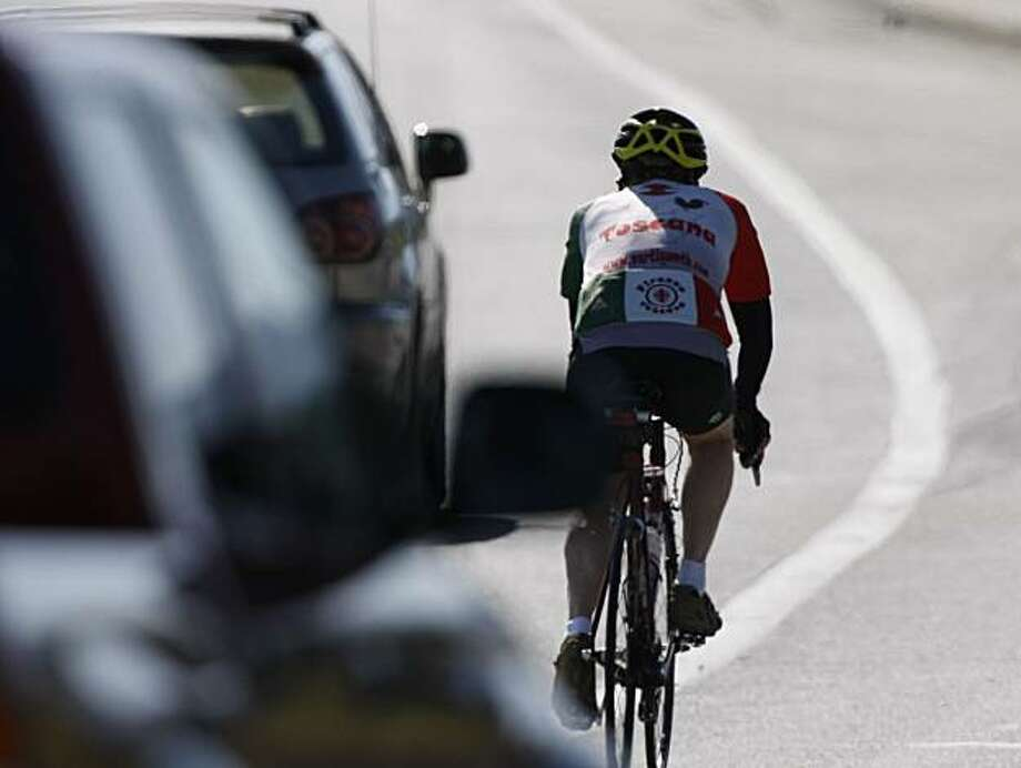 A cyclist, despite being in a bike lane is still very vulnerable to traffic on Sand Hill Road in Menlo Park, Calif. Photo taken on March 20, 2008. Photo by Michael Maloney / San Francisco Chronicle Photo: Michael Maloney, SFC