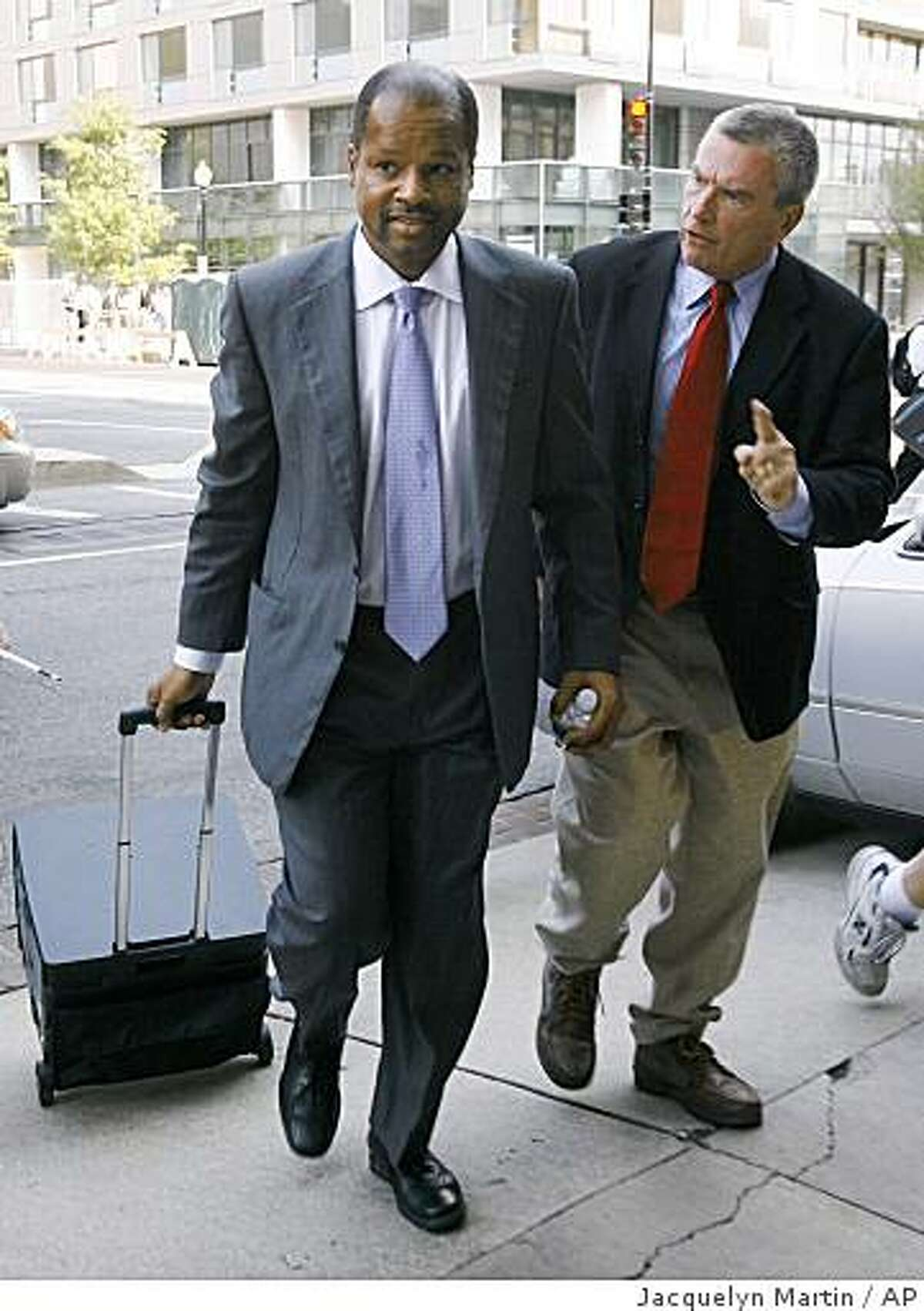 **FILE**In this file photo from June 13, 2007, Roy Pearson, left, is questioned by a member of the media as he leaves court after the second day of his lawsuit over a missing pair of pants in Washington. Pearson returned to court Wednesday, Oct. 22, 2008, over a year after his claim was rejected of being defrauded by a