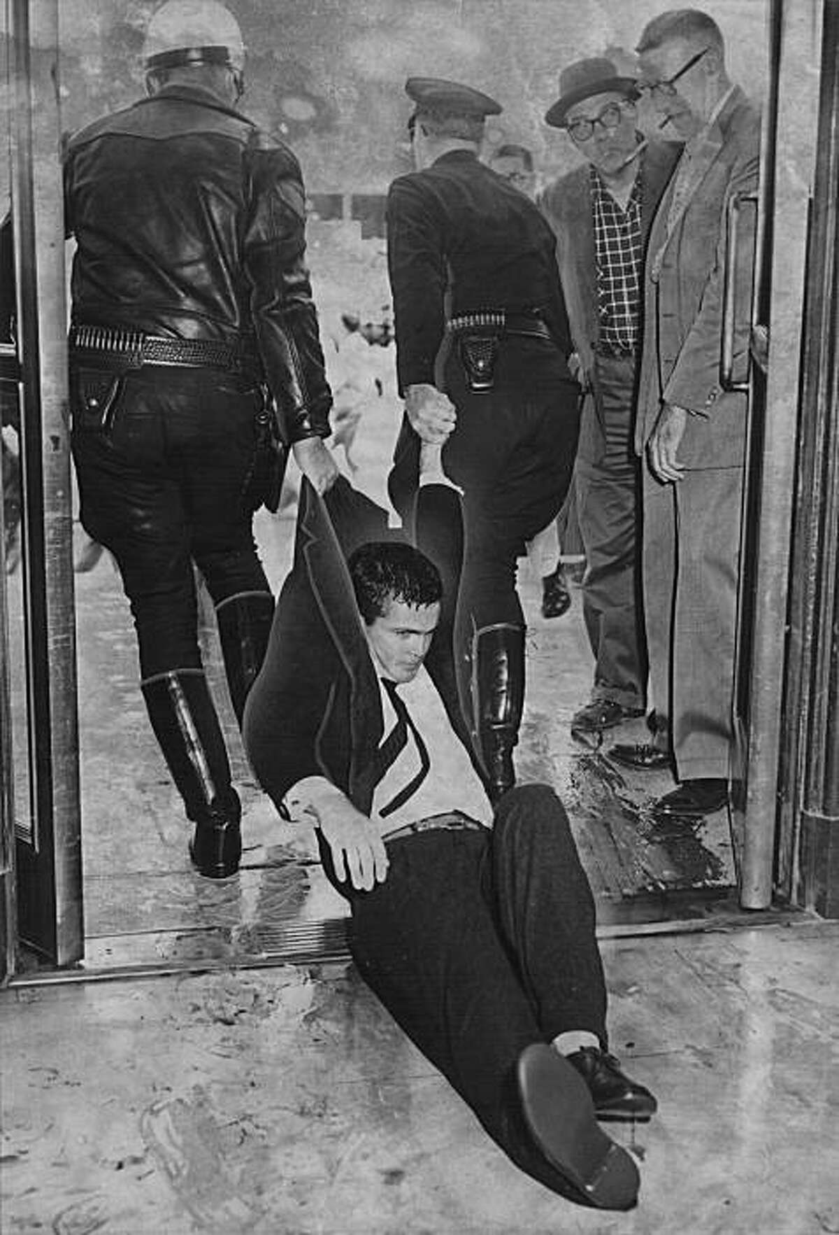 Two San Francisco police officers drag a young demonstrator out a City Hall door. He was one of 64 people taken to jail. Photo taken May 14, 1960.Two San Francisco police officers drag a young demonstrator out a City Hall door. He was one of 64 people taken to jail. Photo taken May 14, 1960.