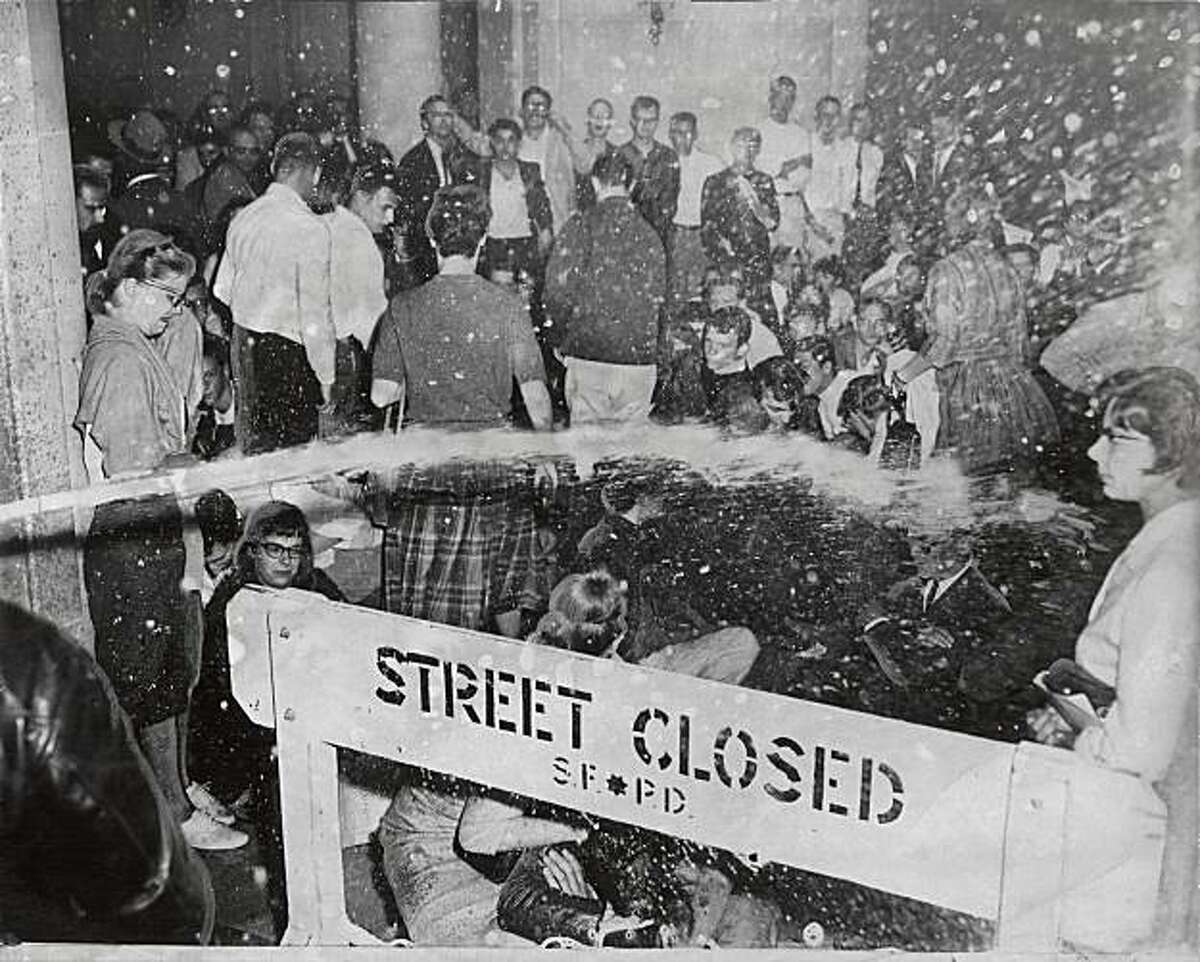 Water from a fire hose poured over a barricade onto demonstrators. Photo taken May 14, 1960.